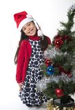 Cute Little Girl in Santa Claus smiling next to Xmas tree Stock Photos