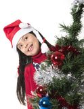 Cute Little Girl in Santa Claus smiling next to Xmas tree Royalty Free Stock Image
