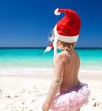 Cute little girl in Santa hat on beach Stock Photos