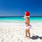 Cute little girl in Santa hat on beach Royalty Free Stock Image