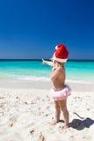 Cute little girl in Santa hat on beach Royalty Free Stock Photo