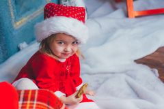 Cute little girl in Santa hat with cookies at home. Beautiful little girl with milk and cookies for Santa Claus in festively decorated room Stock Photography