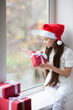 Cute little girl in Santa hat dreaming by the window holding gift Royalty Free Stock Images