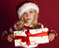 Cute little girl in santa hat holding christmas present Royalty Free Stock Photography