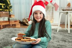 Cute little girl in Santa hat with plate of delicious cookies. At home Royalty Free Stock Photo