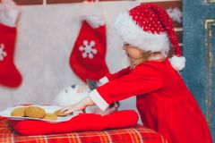 Cute little girl in Santa hat with plate of delicious cookies at home. Beautiful little girl with milk and cookies for Santa Claus in festively decorated room Royalty Free Stock Image
