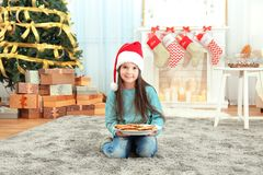 Cute little girl in Santa hat with plate of delicious cookies  at home. Cute little girl in Santa hat with plate of delicious cookies at home Stock Photo