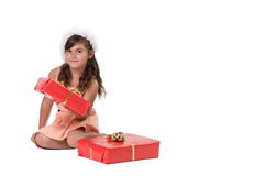 Cute little girl in a Santa hat is sitting royalty free stock photo