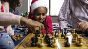 Cute little girl in santa hat watching chess game stock video