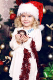 Cute little girl in Santa's hat decorating Christmas tree Royalty Free Stock Photo