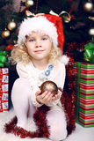 Cute little girl in Santa's hat sitting beside a Christmas tree Royalty Free Stock Image