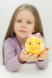Cute little girl saving money in a piggy-bank. Cute little girl saving money in a yellow piggy-bank Royalty Free Stock Images