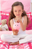 Cute little girl saving money in a piggybank. In her bedroom Royalty Free Stock Image