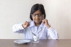 Cute little girl scientist conducting an experiment stock photo