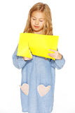 Cute little girl with scissors and yellow paper. Little cute girl making handmade yellow hearts Royalty Free Stock Photos