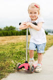 Cute little girl on scooter Royalty Free Stock Photography
