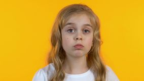 Cute little girl scratching head, trying to remember info, isolated background. Stock footage stock footage