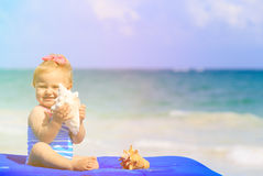 Cute little girl with seashells on the beach Royalty Free Stock Images