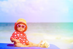 Cute little girl with seashells on the beach Stock Images