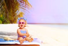 Cute little girl with seashells on summer beach Stock Photo