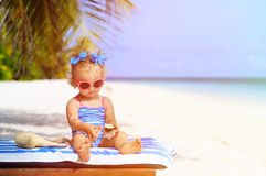 Cute little girl with seashells on summer beach Royalty Free Stock Photography