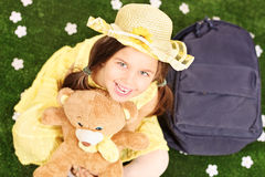 Cute little girl seated on green grass holding a teddy bear. With backpack on the ground next to her Stock Images