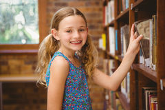 Cute little girl selecting book in library. Portrait of cute little girl selecting book in the library Stock Images