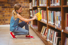 Cute little girl selecting book in library Royalty Free Stock Photos