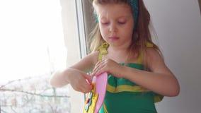 Cute little girl sews a pink handbag. stock footage