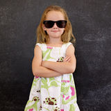 Cute little girl in shades against a black wall Royalty Free Stock Photos