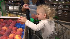 Cute little girl in shopping car help mother to pick peach fruits in supermarket
