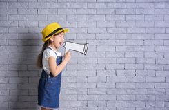 Adorable little girl with paper megaphone on brick wall background. Cute little girl shouting into paper megaphone near brick wall background Royalty Free Stock Photography