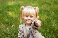 Cute little girl show thumb up. And smile outdoors Stock Photography
