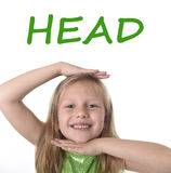 Cute little girl showing head in body parts learning English words at school Royalty Free Stock Photography