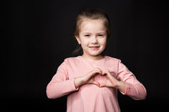 Cute little girl. Showing heart sign on black Royalty Free Stock Photo