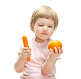 Cute little girl showing orange and carrot Stock Photography