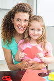 Cute little girl showing paper heart sitting on mothers lap Stock Photos