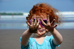 Cute little girl showing sandy hands on the Bali beach Royalty Free Stock Images