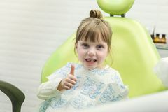 Cute little girl showing thumb up sign at dentist`s office clin. Cute little girl showing thumb up sign at dentist`s office  clinic Stock Images