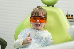 Cute little girl showing thumb up sign at dentist`s office clin. Cute little girl showing thumb up sign at dentist`s office Royalty Free Stock Photos