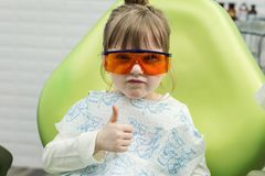 Cute little girl showing thumb up sign at dentist`s office clin. Cute little girl showing thumb up sign at dentist`s office  clinic Stock Image