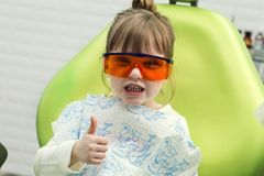 Cute little girl showing thumb up sign at dentist`s office clin. Cute little girl showing thumb up sign at dentist`s office  clinic Royalty Free Stock Photo