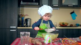Cute little girl sifting flour for cake on kitchen table stock video