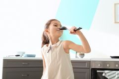 Cute little girl signing song into spoon. In kitchen Stock Image