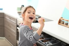 Cute little girl signing song into spoon. In kitchen Royalty Free Stock Image