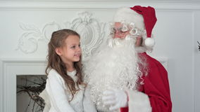 Cute little girl singing a Christmas song sitting on Santa Claus lap stock footage