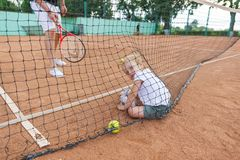 Cute little girl sit at the tennis court. Royalty Free Stock Photography