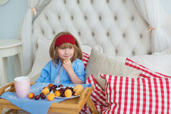 Cute little girl sits at breakfast on a bed Royalty Free Stock Photography