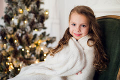 Cute little girl sits by the christmas tree, wrapped in a warm blanket at home Stock Photo