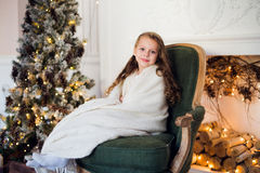 Cute little girl sits by the christmas tree, wrapped in a warm blanket at home Royalty Free Stock Photos